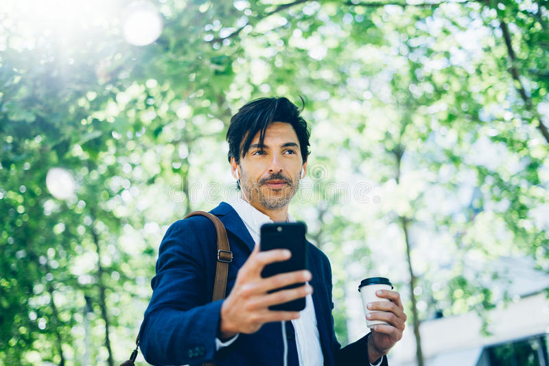 Стильный молодой бизнесмен используя smartphone для listining музыки пока идущ в парк города и держащ кофе взятия отсутствующий стоковые изображения