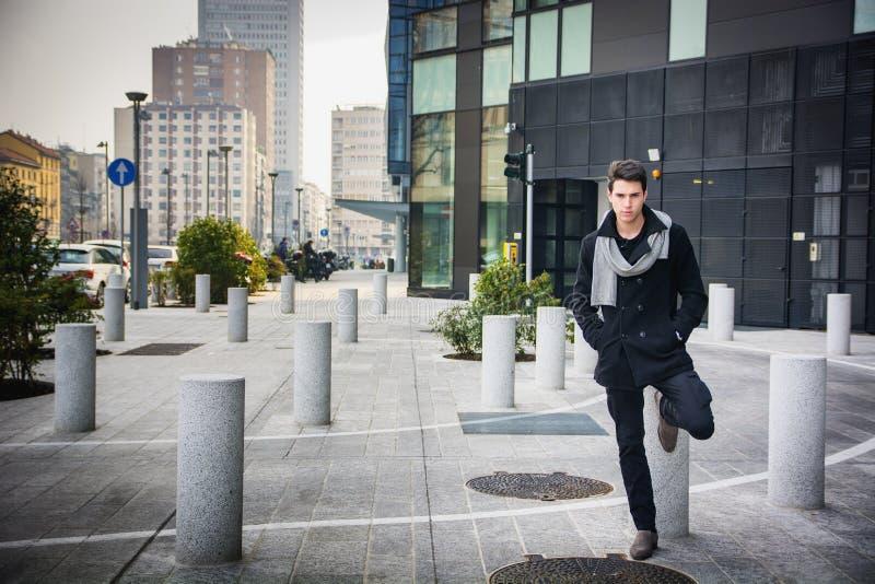 Стильный молодой красивый человек в черном положении пальто стоковое изображение rf