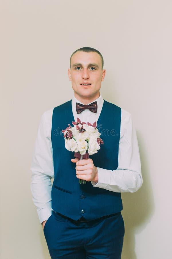 Стильный одетый человек держа элегантный букет роз представляя на пустой белой предпосылке стоковые фотографии rf