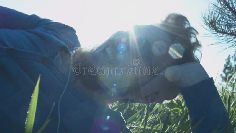 Стильный счастливый человек с стеклами смеется над лежать на траве в наушниках Человек с его propps руки его голова и акции видеоматериалы