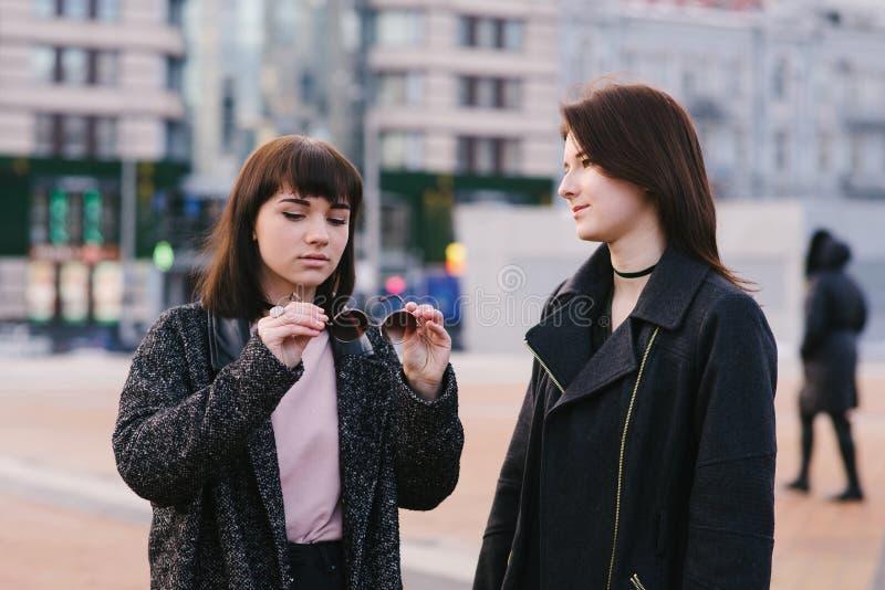 2 стильных молодых подруги нося вскользь прогулку вокруг города и связывают одна девушка держа солнечные очки стоковое изображение
