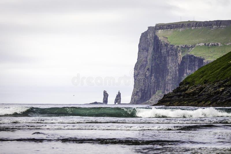 Стога моря Risin и Kellingin в расстоянии, при большая волна причаливая заливу Tjornuvik, Streymoy, Фарерские острова (Faroes&# стоковые изображения