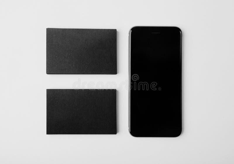 2 стога пустых черных визитных карточек и smartphone на белой предпосылке горизонтально стоковое изображение