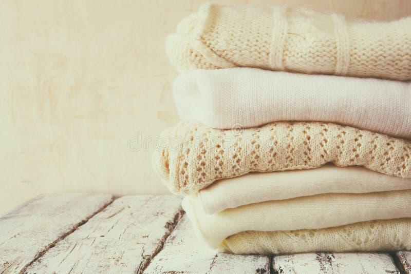 Стог белых уютных связанных свитеров на деревянном столе стоковые изображения rf