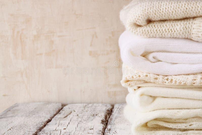 Стог белых уютных связанных свитеров на деревянном столе стоковое изображение rf