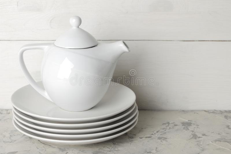 Стог блюд tableware на светлой конкретной предпосылке блюда для служения таблицы белые плиты и чайник стоковое фото