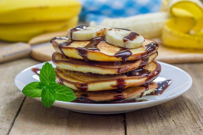 Стог блинчиков с сиропом банана и шоколада стоковые изображения rf