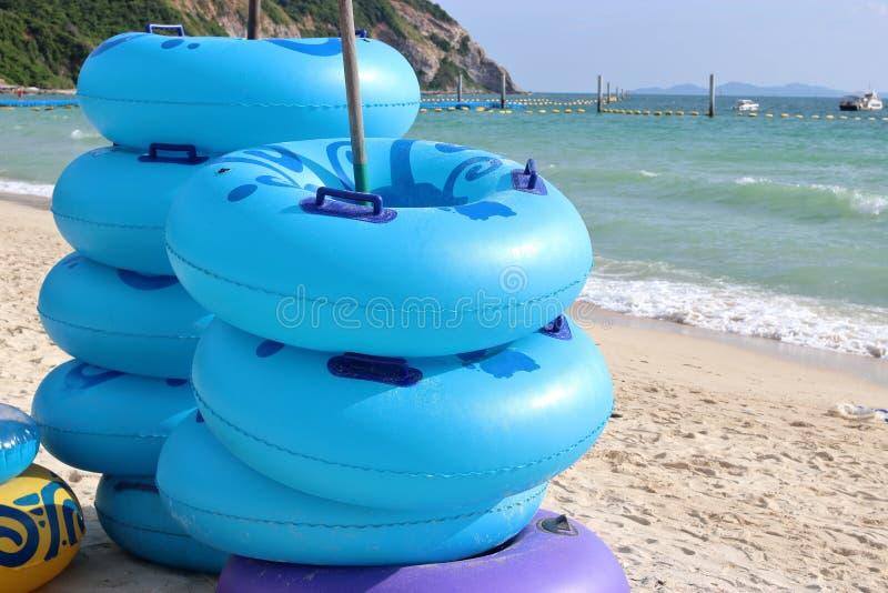 Стог голубой плавать звенит на береговой линии, кольце заплыва, резиновом кольце, плавая трубки стоковые фото