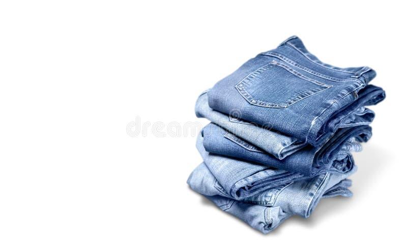 Стог джинсов джинсовой ткани изолированных на белизне стоковые изображения