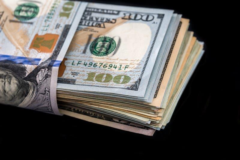 стог доллара изолированный на черноте стоковые изображения