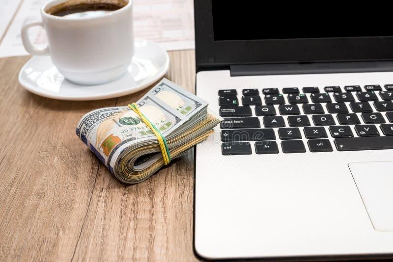 Стог доллара, чашки кофе и компьтер-книжки на столе стоковое изображение