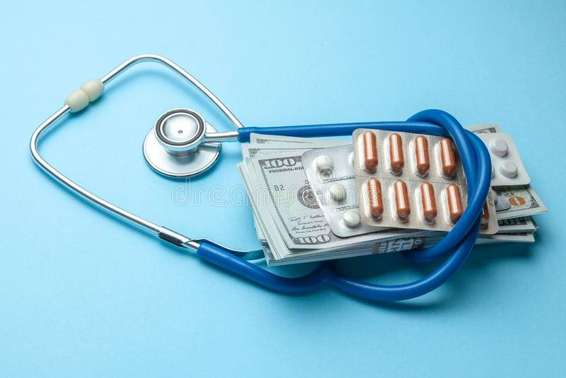 Стог долларов и таблеток наличных денег в волдыре со стетоскопом на голубой предпосылке Концепция медицинского strechevka или дор стоковые фотографии rf