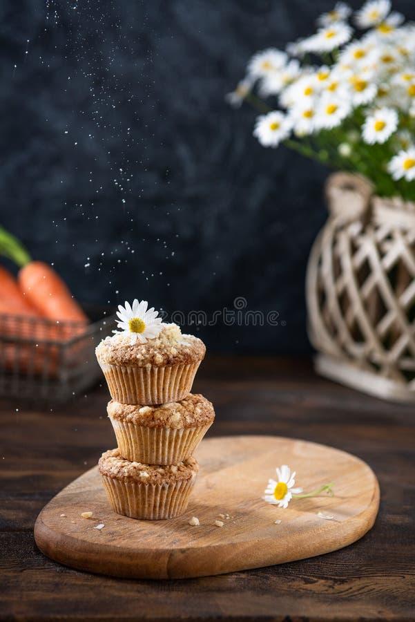 Стог домодельных булочек моркови с высушенными плодами и гайками на деревянной доске, букета стоцвета и моркови на таблице E стоковая фотография rf