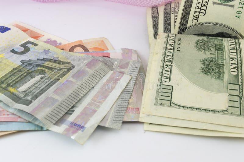 Стог евро и долларовых банкнот на таблице стоковые фото