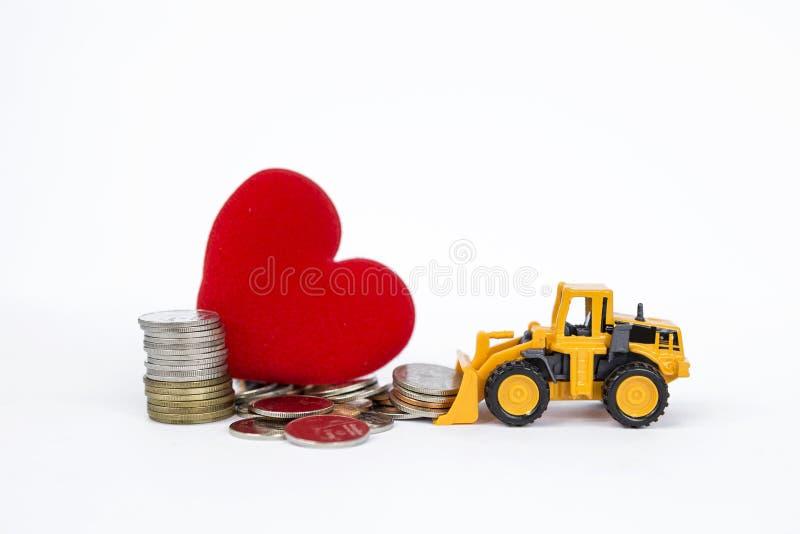 Стог желтого переднего затяжелителя moving монеток с кучей монеток и красного сердца на предпосылке стоковое изображение rf