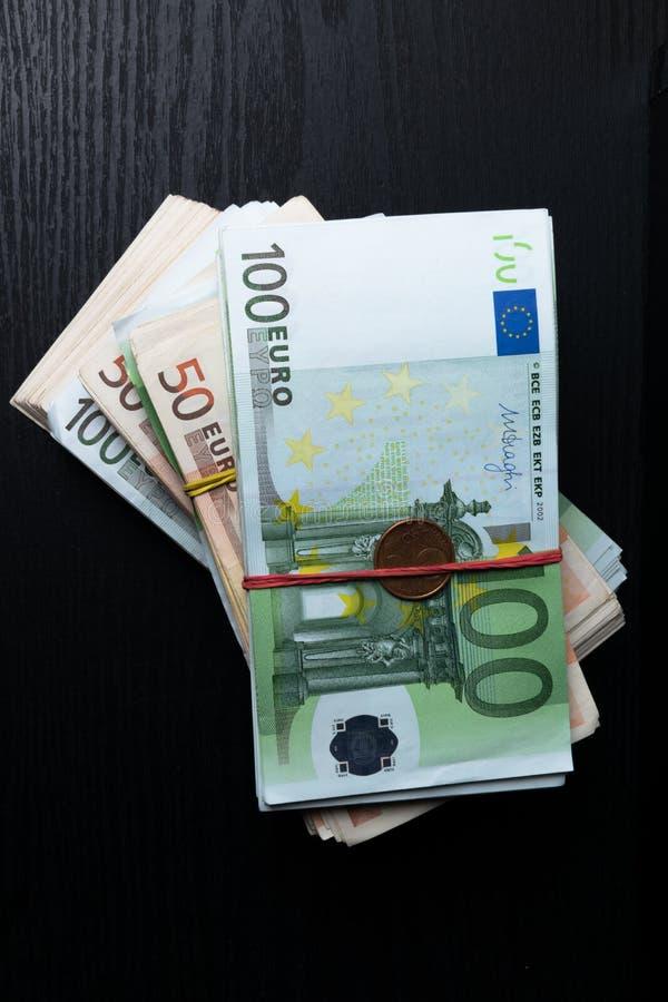 Стог изолированных банкнот и монеток евро 50, 100, банкноты евро Европейские банкноты денег валюты изолированные на черном backgr стоковое изображение rf