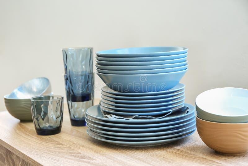 Стог керамических плит, шаров и стекел на деревянном столе стоковая фотография