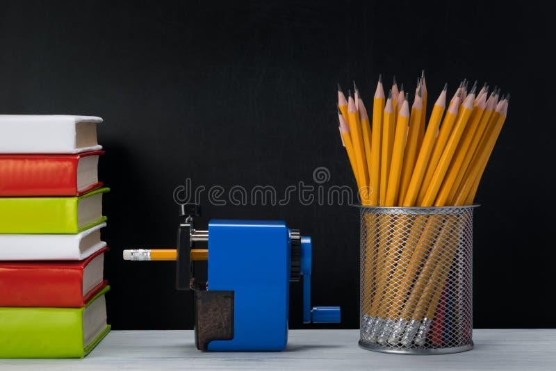Стог книг и карандашей на темной таблице предпосылки стоковые фото