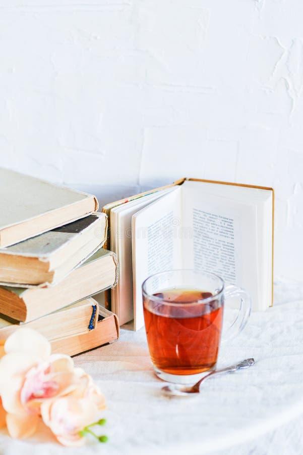 стог книг, книги и чая в стеклянной чашке на яркой предпосылке с ветвью орхидеи, концепцией влюбленности чтения, времени t стоковые изображения