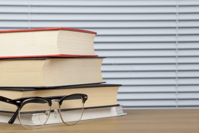 Стог книг на таблице с стеклами глаза стоковая фотография