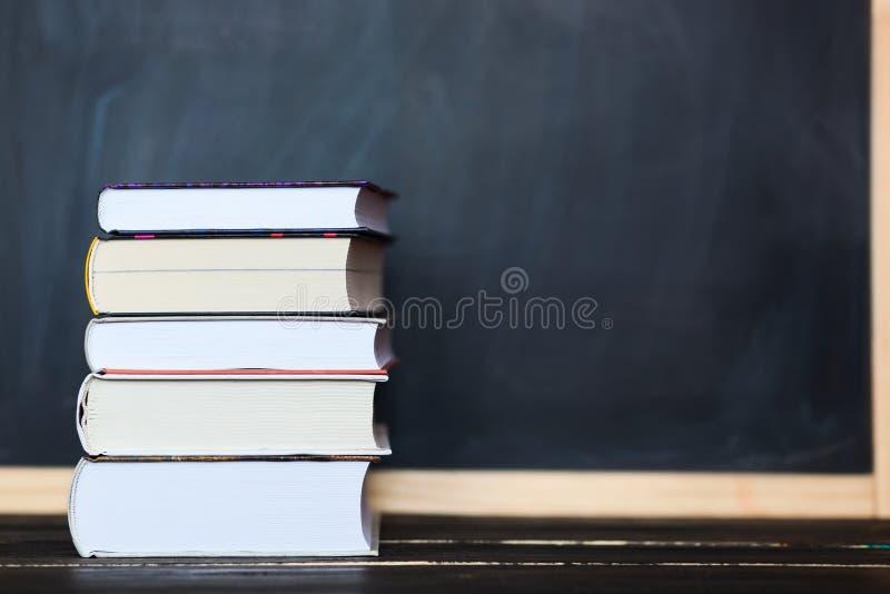 Стог книг с доской в предпосылке Космос для вашего te стоковое фото rf
