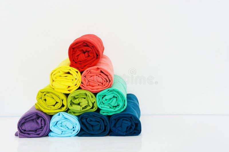 Стог красочной футболки свернутый вверх на белой предпосылке стоковые изображения rf