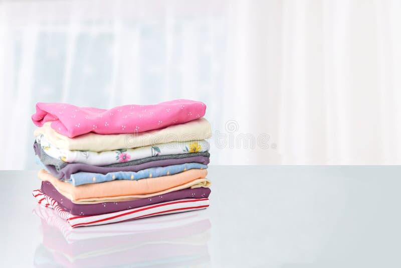 Стог красочных милых одежд девушки Куча красочные одежды на белой таблице против яркой абстрактной запачканной предпосылки стоковое изображение