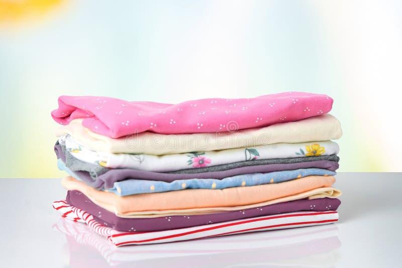 Стог красочных милых одежд девушки Куча красочные одежды на белой таблице против яркой абстрактной запачканной предпосылки стоковое фото