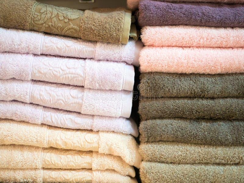 Стог красочных сложенных полотенец Terry Дом магазина Многочисленные полотенца штабелированные и сложенные на полках магазина стоковые фото
