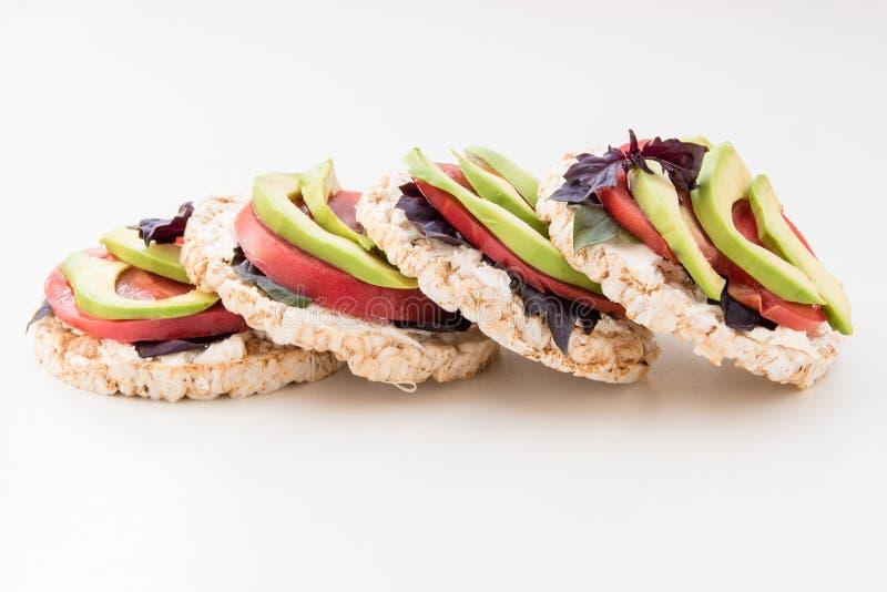 Стог круглых crispbreads с сыром, томатами, авокадоом и базиликом стоковые фотографии rf