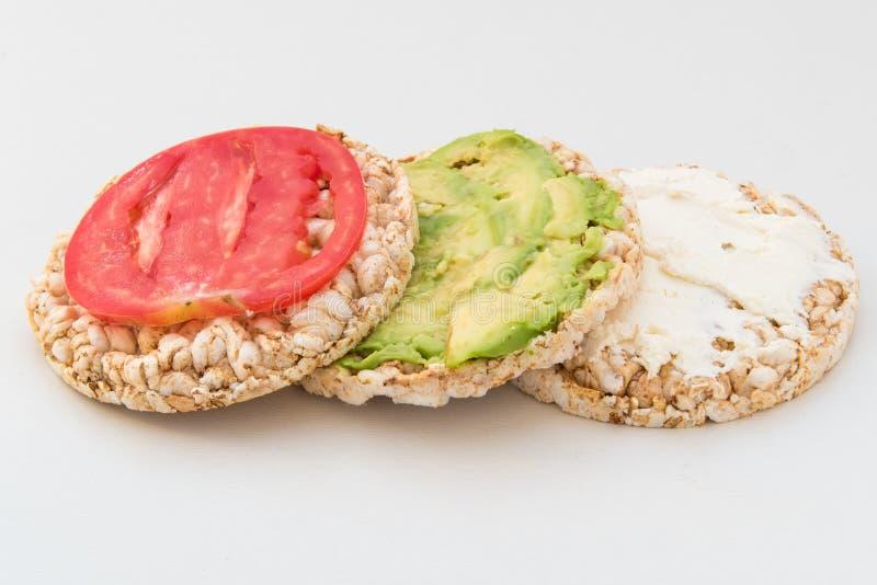 Стог круглых crispbreads с сыром, томатами, авокадоом и базиликом стоковые изображения rf