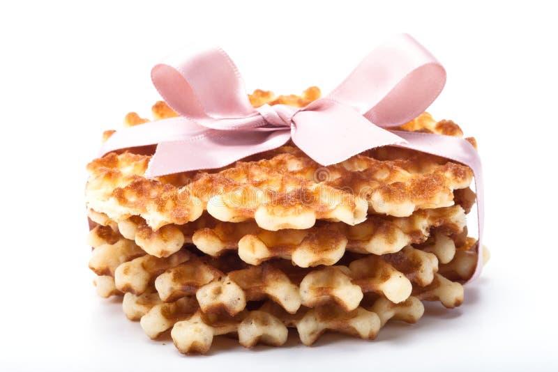 Стог круглых waffles на белой предпосылке с розовой лентой стоковое изображение