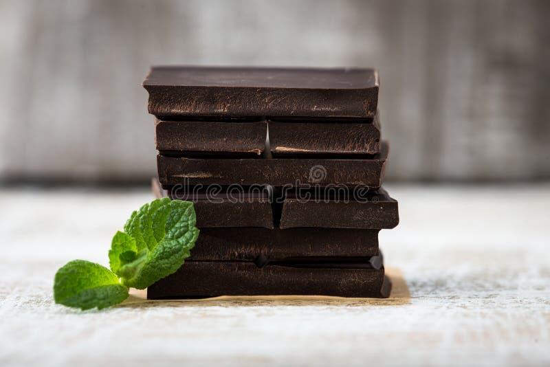 Стог кусков шоколада с лист мяты темный шоколад над wo стоковое изображение