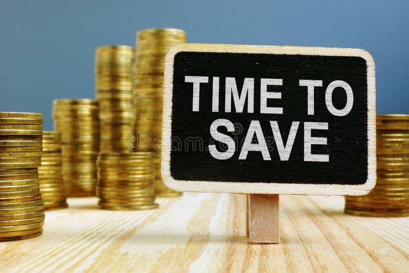 Стог монеток и времени знака сохранить деньги стоковое фото