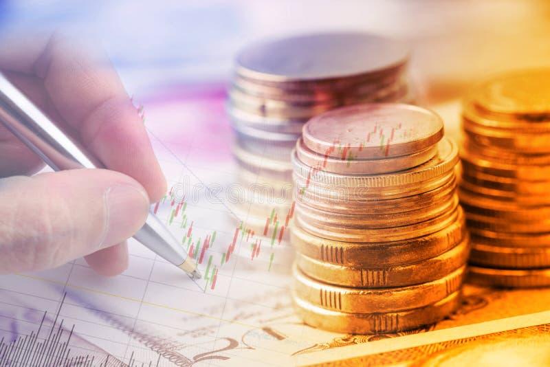 Стог монеток и руки держа ручку шариковой авторучки рассматривает техническую диаграмму финансового дочумента стоковая фотография