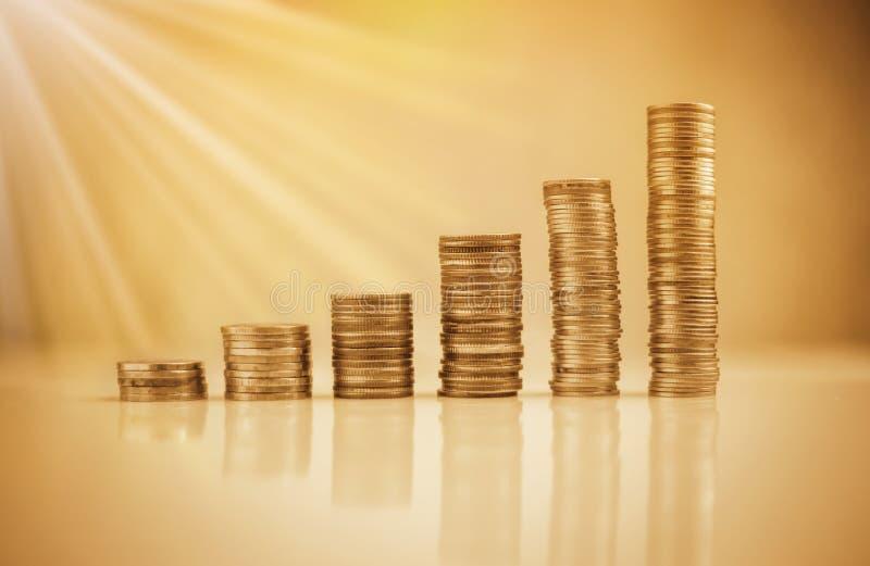 Стог монеток на белом againt пола с bokeh нерезкости стоковое фото