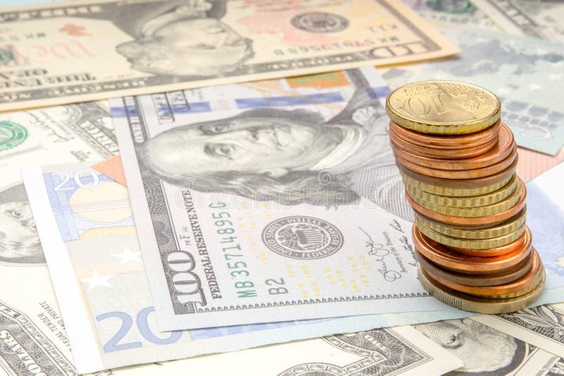 Стог монеток на предпосылке различных банкнот евро и доллара стоковая фотография rf