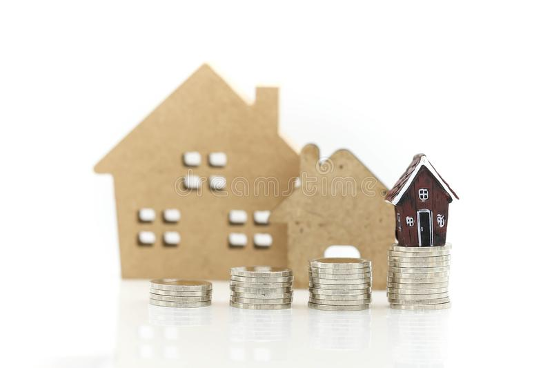 Стог монеток с мини домом, финансами дела, сбережениями и домом стоковые фото