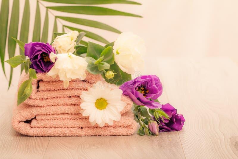 Стог мягких полотенец Terry с белыми и фиолетовыми цветками и зелеными листьями стоковое изображение rf