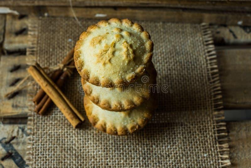 Стог рождества семенит пироги на дерюге на винтажной деревянной коробке, с ручками циннамона, взгляд сверху, положение квартиры,  стоковые изображения rf