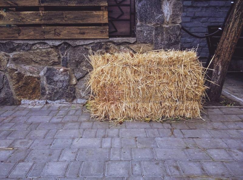 Стог сена лежит на городских вымощая плитах Деревня в городе стоковые изображения