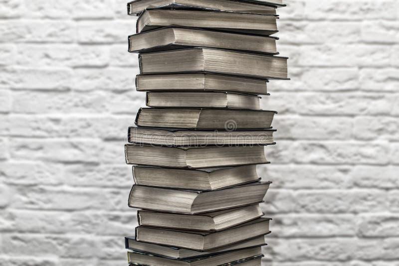 Стог старых книг на предпосылке кирпичной стены стоковые фото