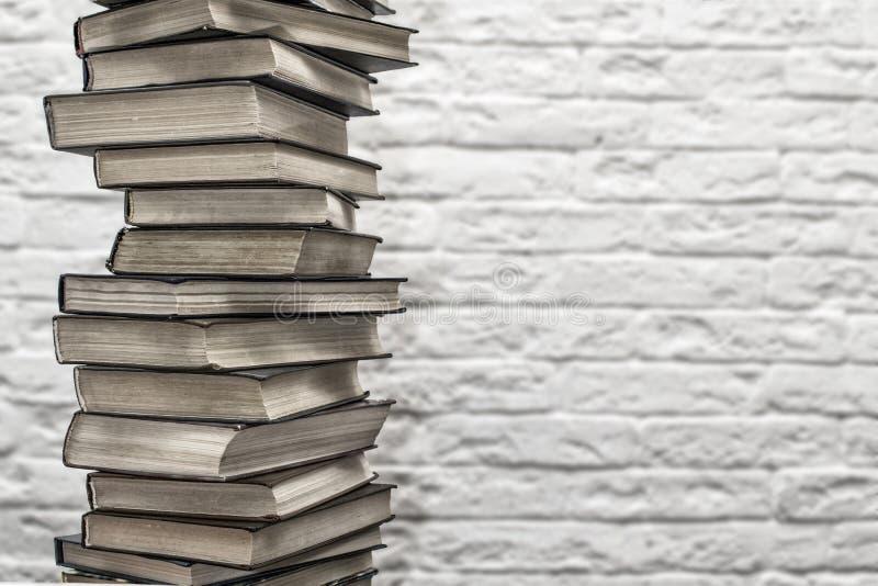 Стог старых книг на предпосылке кирпичной стены стоковая фотография