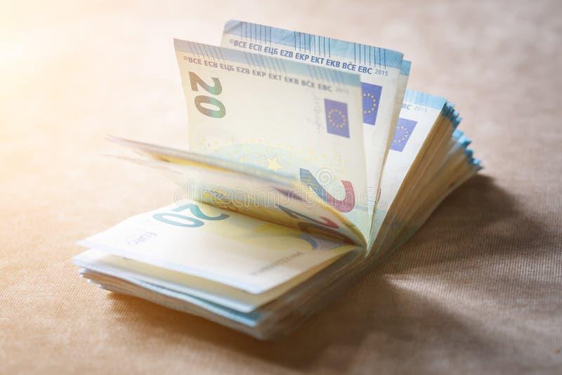Стог стоимости денег 20 лож евро на русой поверхности ткани в лучах солнца стоковые фотографии rf