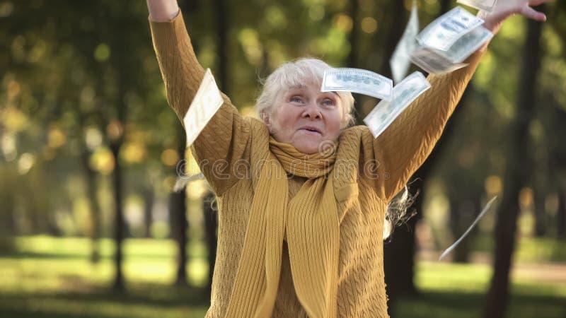 Стог счастливой старшей пожилой женщины бросая долларовых банкнот в парке, запланированного выхода на пенсию стоковая фотография