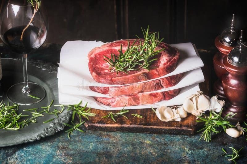 Стог сырцовых стейков с розмариновым маслом, специями и травой красного вина на кухонном столе на темной деревянной предпосылке стоковые изображения