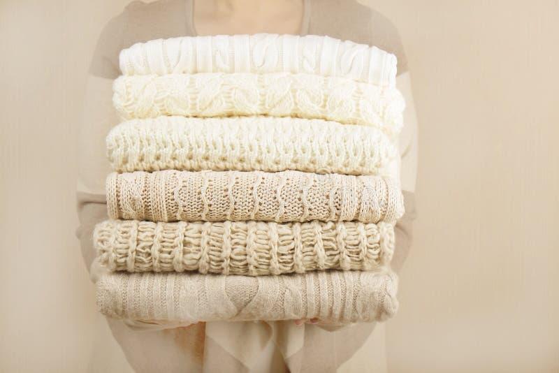 Стог теплых пастельных свитеров, держа в руках женщины стоковая фотография