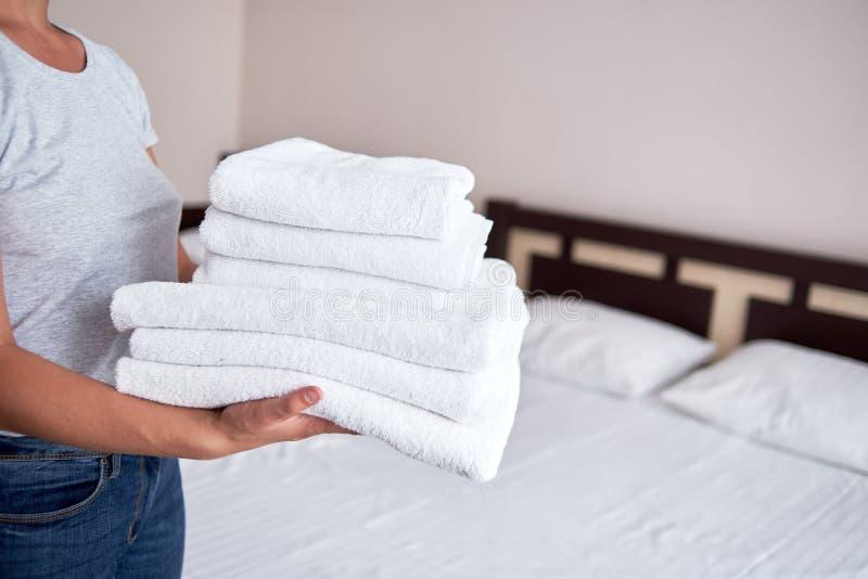 Стог удерживания женщины белых чистых полотенец ванны в интерьере спальни, космосе экземпляра Закройте вверх по рукам горничной г стоковые фото