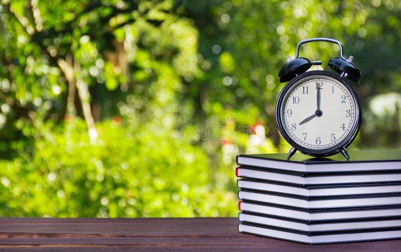 Стог учебников и часов на деревянном столе Стог книг и будильника на зеленом цвете запачкал предпосылку воспитательно стоковые фотографии rf