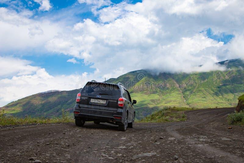 Стойка автомобиля Forester Subaru на грязной улице в зеленых горах стоковые изображения